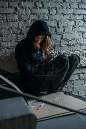 hooded heroin addicted junkie sitting on stairs with syringes