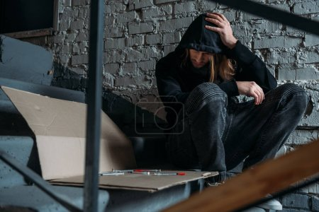 Photo for Heroin addicted junkie sitting on stairs with syringes - Royalty Free Image