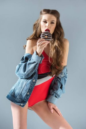sexy girl in red swimsuit eating donut and looking at camera isolated on grey