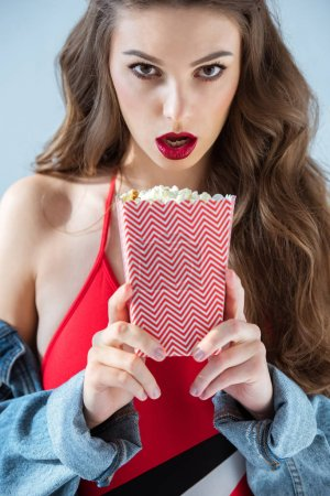 surprised sexy girl holding popcorn and looking at camera