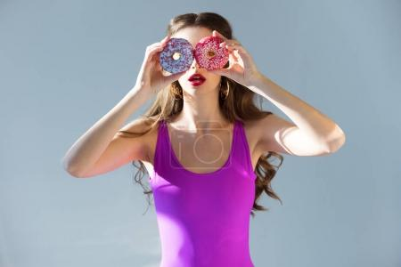 sexy attractive girl in ultra violet swimsuit covering eyes with donuts isolated on grey