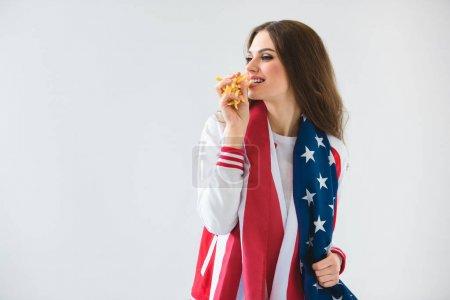 Photo pour Sexy jeune fille souriante avec drapeau usa, manger des frites français isolé sur blanc - image libre de droit