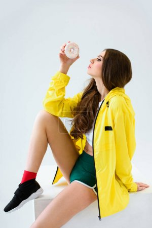 Photo for Side view of sexy girl in yellow jacket and shorts sitting on cube with donut isolated on white - Royalty Free Image