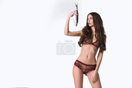 Photo for Surprised sexy girl in lace lingerie looking at herring isolated on white - Royalty Free Image
