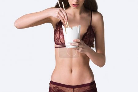 cropped image of sexy girl in lace lingerie taking noodles with chopsticks isolated on white