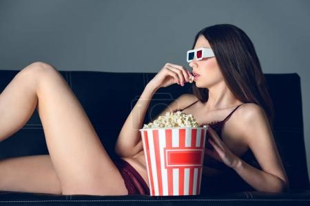 side view of sexy girl in lace lingerie and 3d glasses eating popcorn on sofa