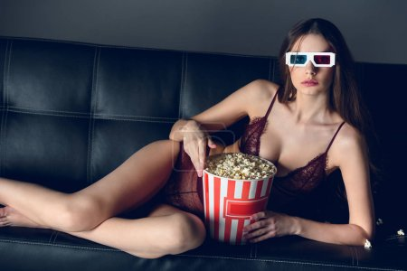 sexy girl in lace lingerie and 3d glasses lying with popcorn on sofa
