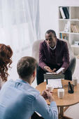 African american counselor talking to divorcing couple in office