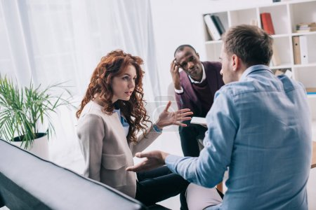 Arguing couple on sofa and african american counselor in office