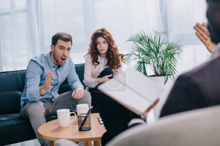 Angry young man with girlfriend sitting on sofa and arguing with counselor