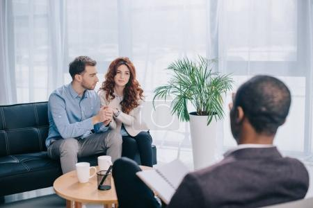 Young couple sitting on sofa in office and psychiatrist with textbook