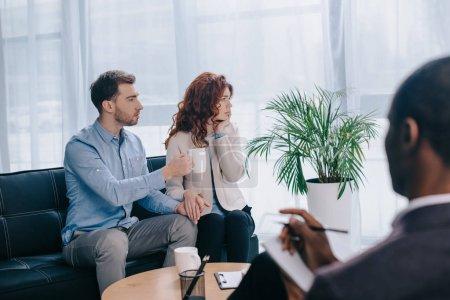 Conseiller afro-américaine avec manuel et un couple qui divorce sur canapé