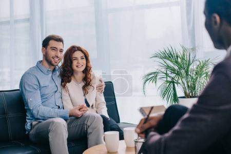 Souriante jeune couple assis sur le canapé et parler au conseiller avec un crayon à la main