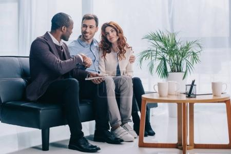 Psychotherapist shaking hand of smiling man with young girlfriend near