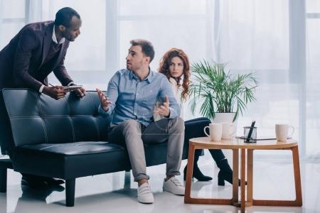 Photo pour Conseiller avec presse-papiers parle de bouleverser le couple assis sur le canapé - image libre de droit