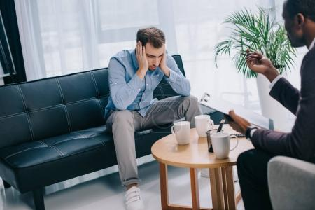 Upset young man sitting on couch and psychiatrist with clipboard