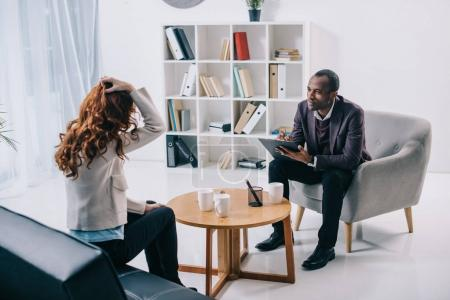 African american psychiatrist sitting in armchair and talking to female patient