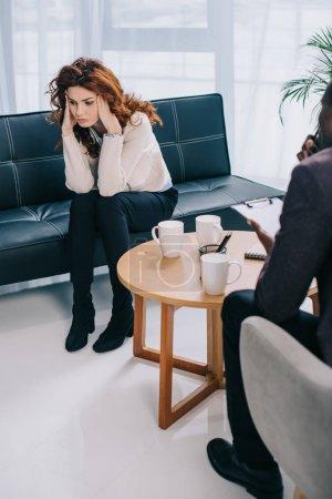 Femme contrariée, assis sur le canapé et psychiatre assis près de