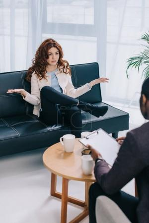 Young woman with wide arms talking to psychiatrist