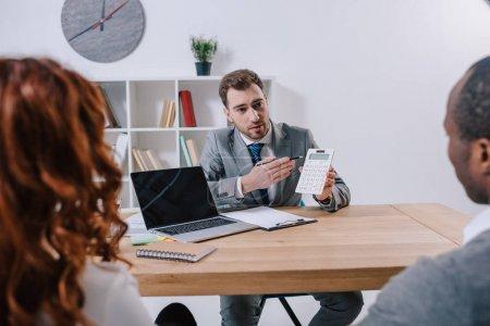 Photo pour Conseiller financier montrant le calcul tandis que les clients assis à table avec ordinateur portable - image libre de droit