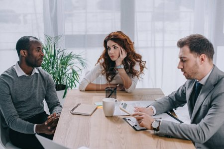 Financial adviser doing calculation while business partners sitting at table
