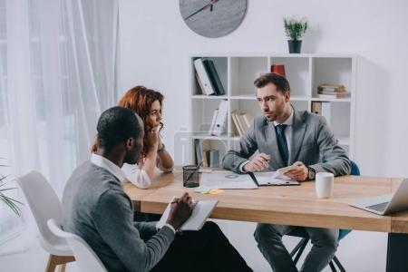 Estate agent with interracial couple sitting at table in office