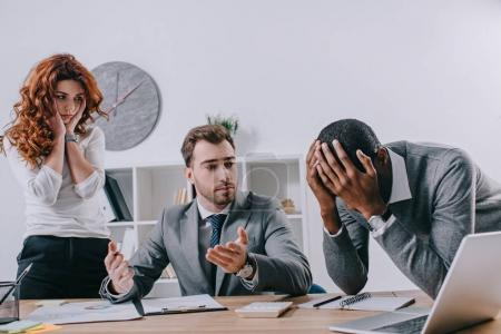 Upset business colleagues and financial adviser in office