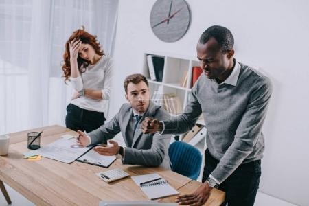 Angry businessman with upset businesswoman and financial adviser sitting at table