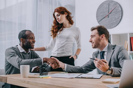Photo pour Couple interracial au bureau de l'agent immobilier - image libre de droit