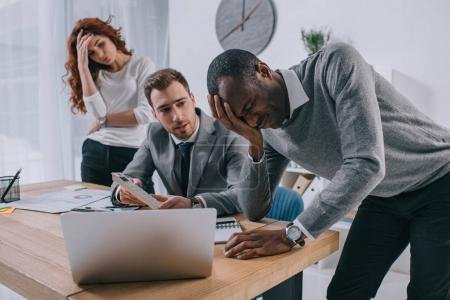 Financial adviser showing calculation to upset business partners