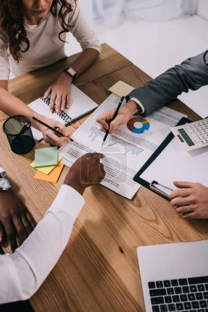 Photo pour Équipe de partenaires commerciaux qui font de la paperasserie pendant qu'ils sont assis à table - image libre de droit
