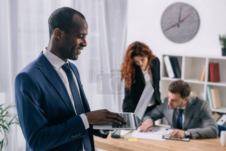 Smiling african businessman with laptop in hands and two business colleagues working at table