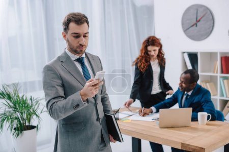 Young stylish businessman with smartphone and two business partners doing paperwork at table