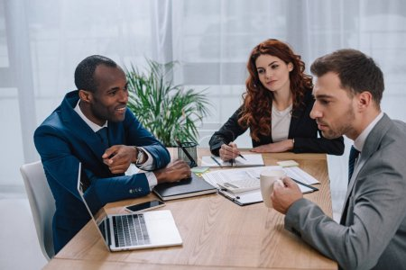 Team of business partners sitting at table with laptop