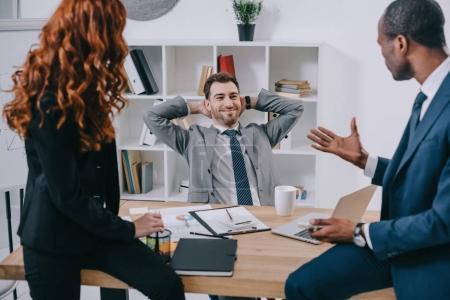 Photo pour Conseiller en investissement souriant assis dans le fauteuil tandis que les partenaires commerciaux de lui parler - image libre de droit
