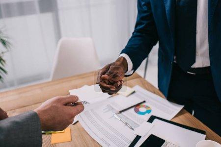 Recadrée vue d'homme d'affaires donnant carte de visite à partenaire africain-américain