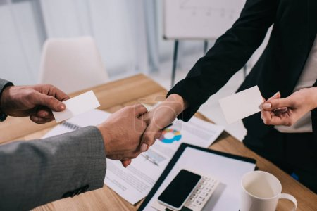 Cropped view of business partners shaking hands and giving visit cards to each other