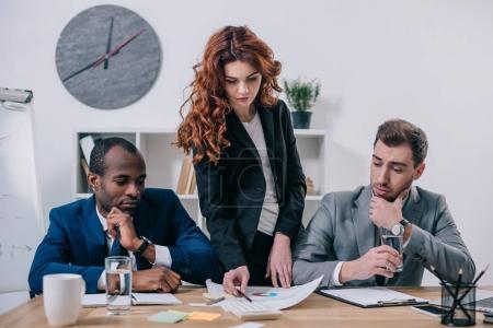 Photo pour Conseiller financier femelle, montrant la présentation aux partenaires d'affaires au bureau - image libre de droit