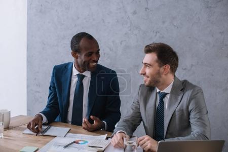 Photo pour Multiethniques hommes d'affaires travaillant à table avec les papiers et ordinateur portable - image libre de droit