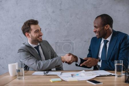 Multicultural business partners shaking hands at working table with documents