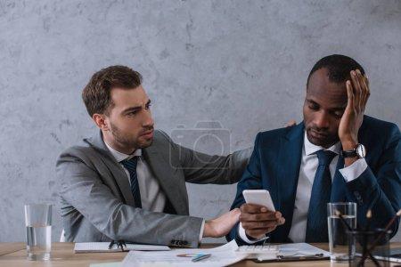 Photo pour Jeune homme d'affaires élégant acclamations bouleverser partenaire avec le smartphone dans la main - image libre de droit