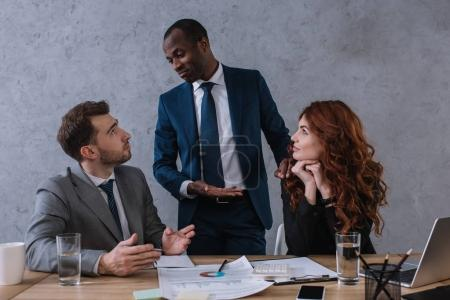 Financial adviser talking to business partners sitting at table