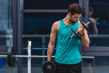 muscular sportsman training with dumbbells in gym
