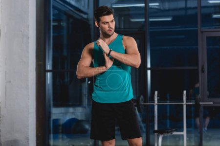 handsome sportsman stretching arms in gym