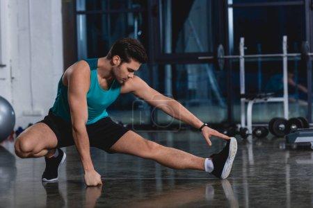 sportsman stretching legs in sports center