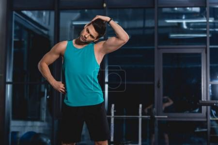 Photo for Sportsman stretching neck in sports hall - Royalty Free Image