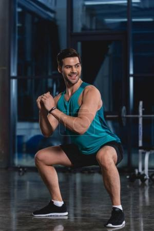 smiling sportsman squatting in sports hall