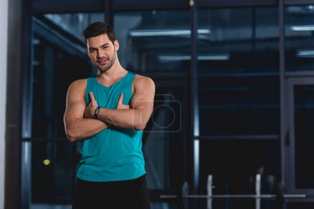 smiling muscular sportsman posing with crossed arms in gym