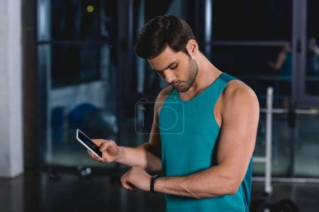 sportsman using fitness tracker and smartphone in gym
