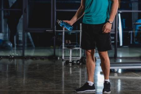 cropped view of sportsman holding sport bottle in sports hall